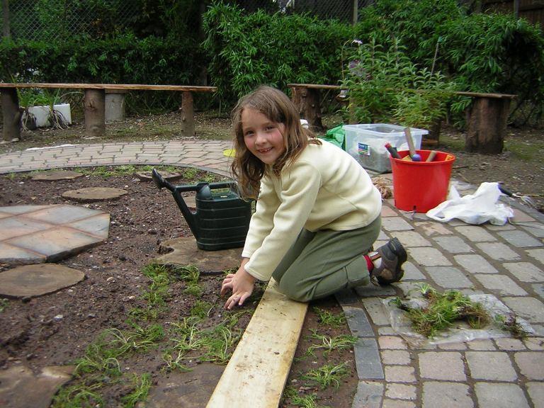 School girl planting chamomile